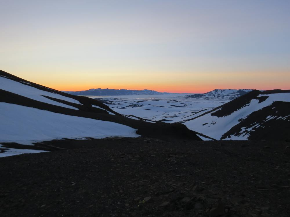 Outlook across empty snowy mountains and valleys at sunset