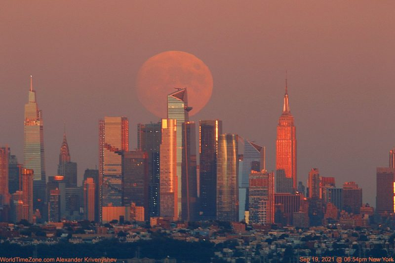A big orange almost-full moon rising over NYC.