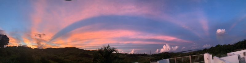 Crepuscular rays: Arc of pink clouds and rays in long, flat picture.