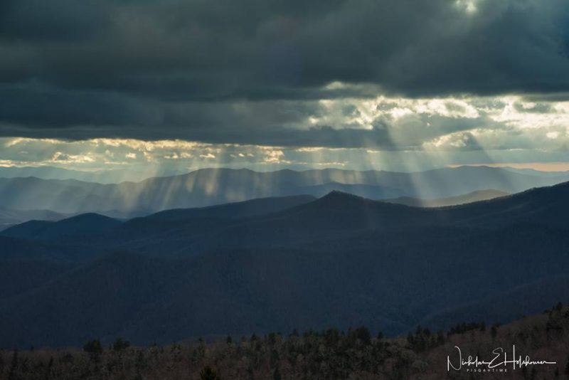 Sunbeams from dark clouds aimed down at mountains.