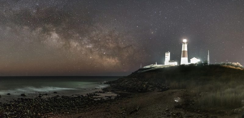 Fuzzy light band across starry sky with brightly-lit lighthouse tower in distance.