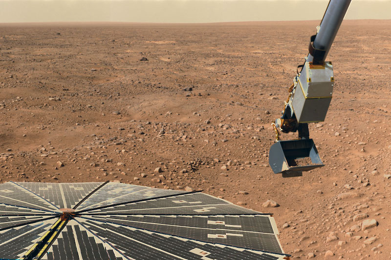 Flat panel and robotic arm with scoop and reddish rocky terrain in background.
