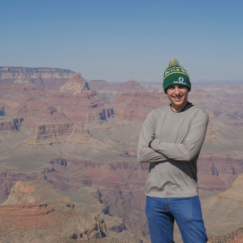 Man in knit cap, long sleeved sweater and jeans, with his arms folded, standing in front of a canyon.