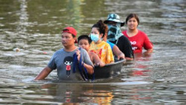 Thai people wade through floodwaters in Chaiyaphum province, north-east of Bangkok, on Tuesday.