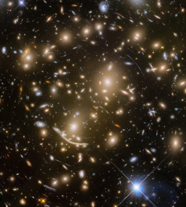 Black background with very many small golden galaxies and numerous arcs.
