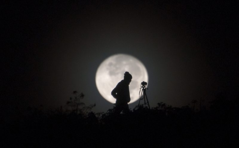 Large full moon, with person and camera on tripod silhouetted against it.