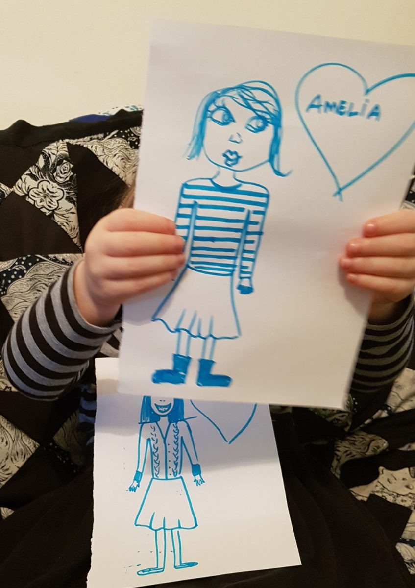 Oppportunity for bonding and language acquisition - child holding drawings