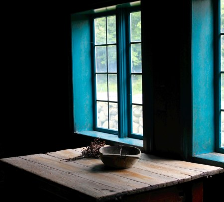 view of a blue-framed window and wooden table with a bowl and foliage on it
