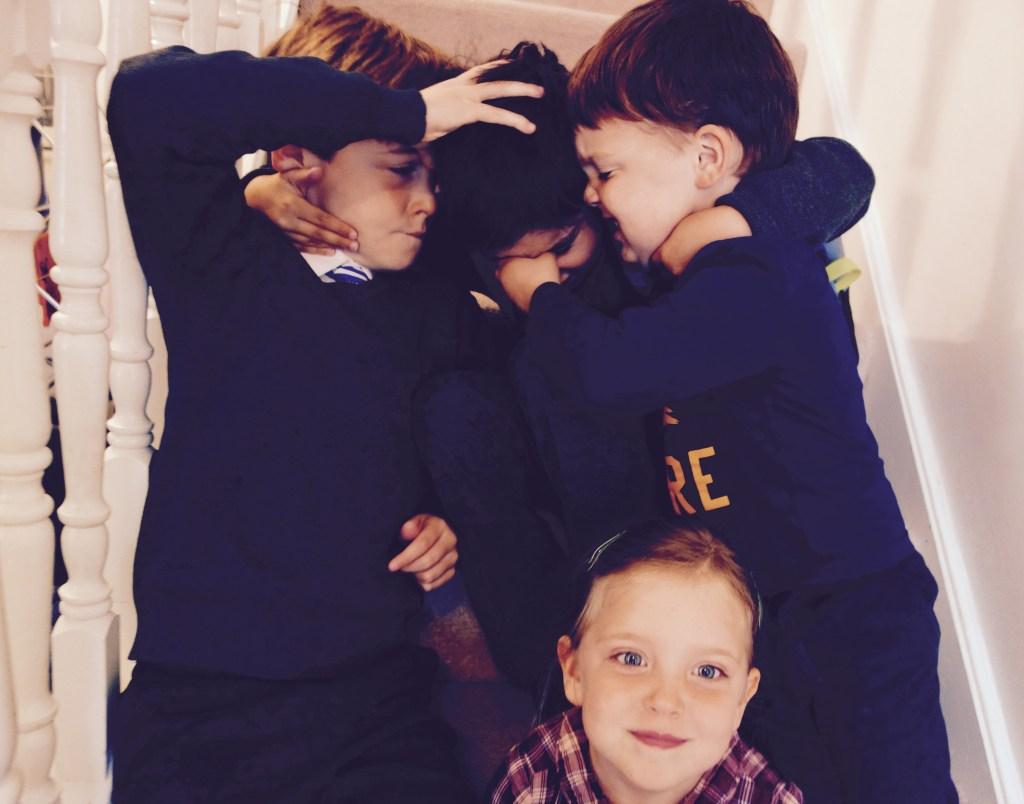 photo of three boys wrestling behind a girl sitting still