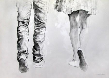 man in jeans and sneakers walking besides women wearing a flowing skirt