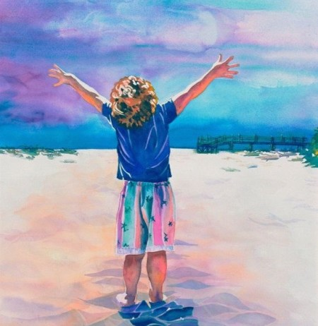joyful young boy with outstretched arms on beach