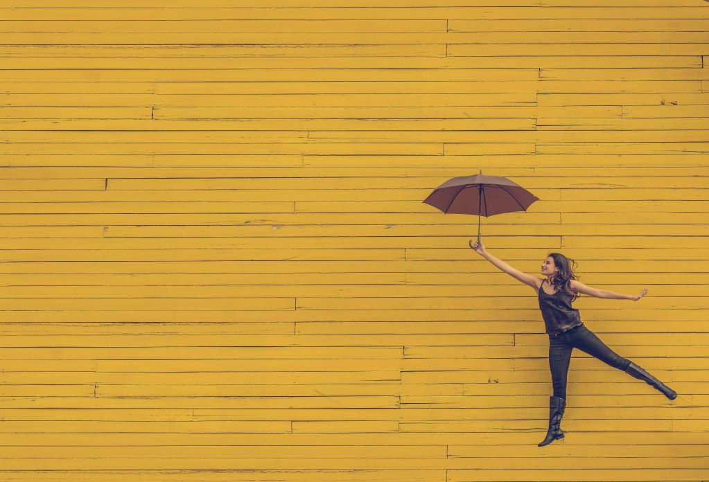 women jumping with umbrella in front of yellow wood-paneled wall