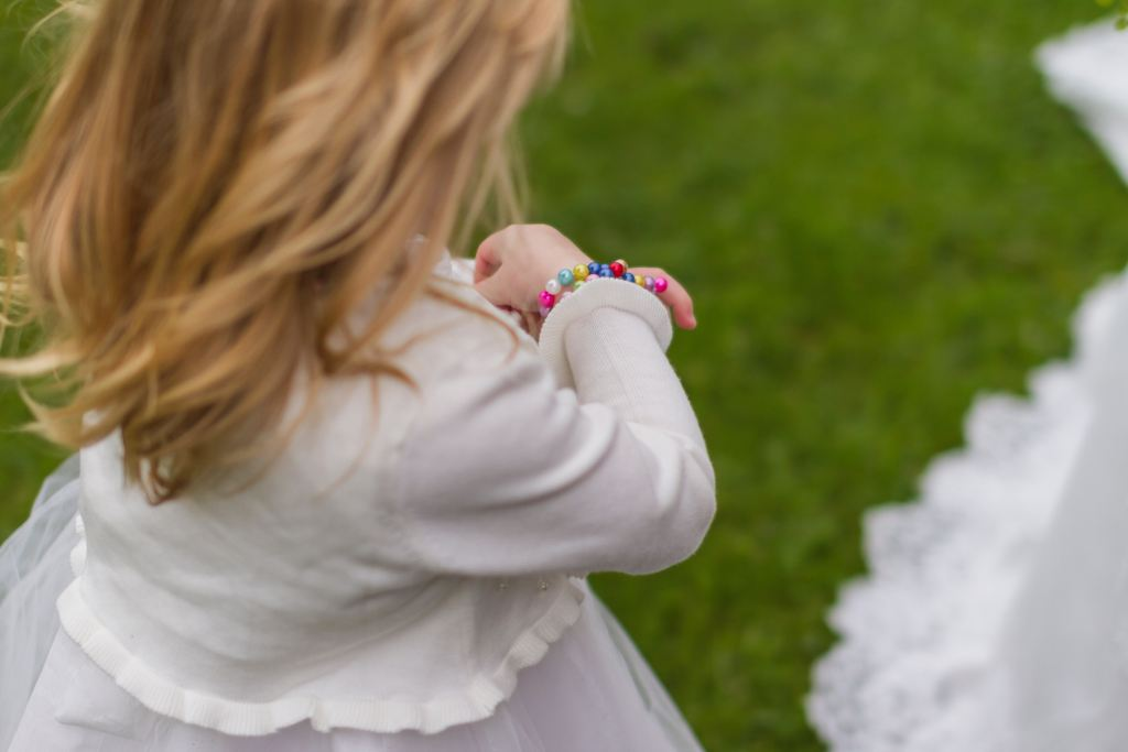 View from behind of a little blonde girl in a white dress wearing a colorful beaded bracelet