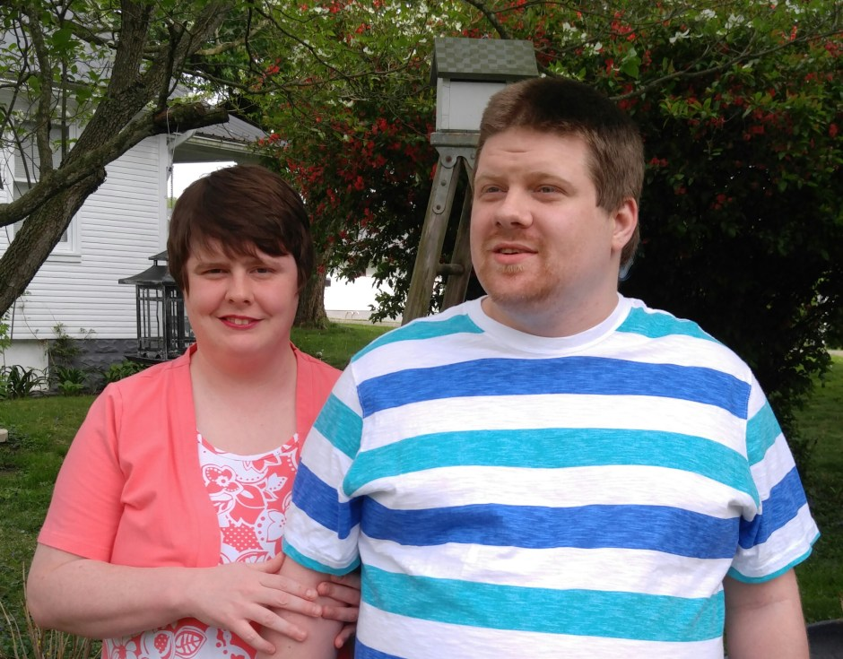 Mom smile while holding arm of adult autistic son in backyard of home