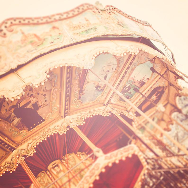 Titled shot of the top of a red and gold carousel with a vintage-like filter.
