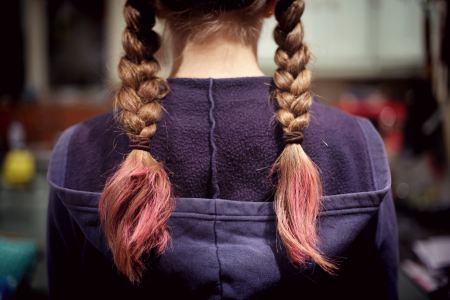 girl wearing blue hooded sweatshirt standing backwards with braids with pink tips