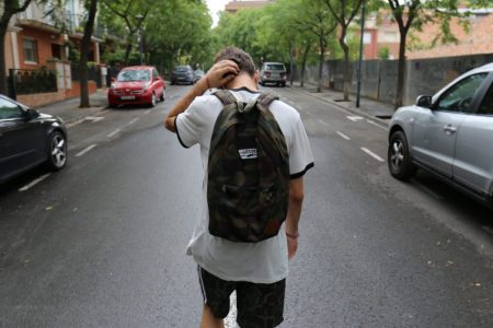 teen boy with backpack walking down street with head down
