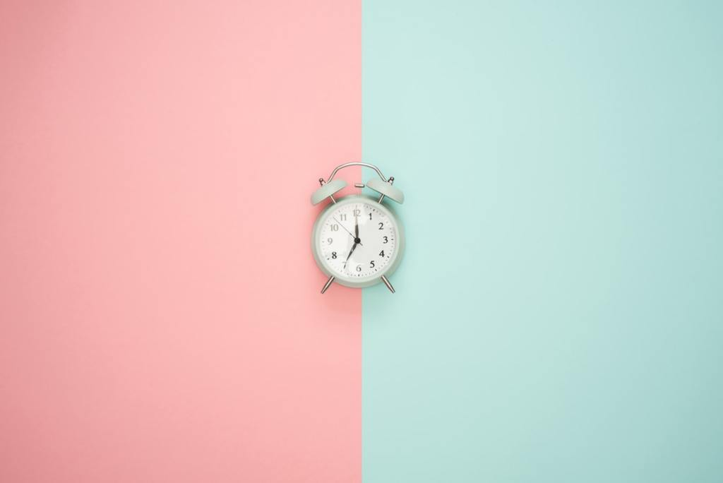 clock against pink and blue background