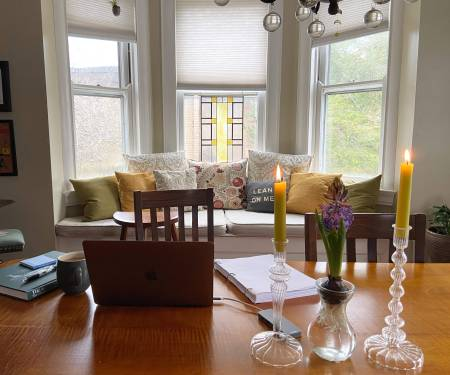 Desk with laptop and candles in front of bay window