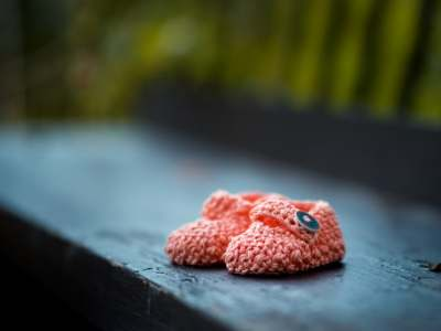 knitted baby shoes on an outside step