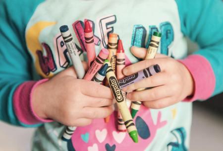 little kid hands holding bundle of crayons