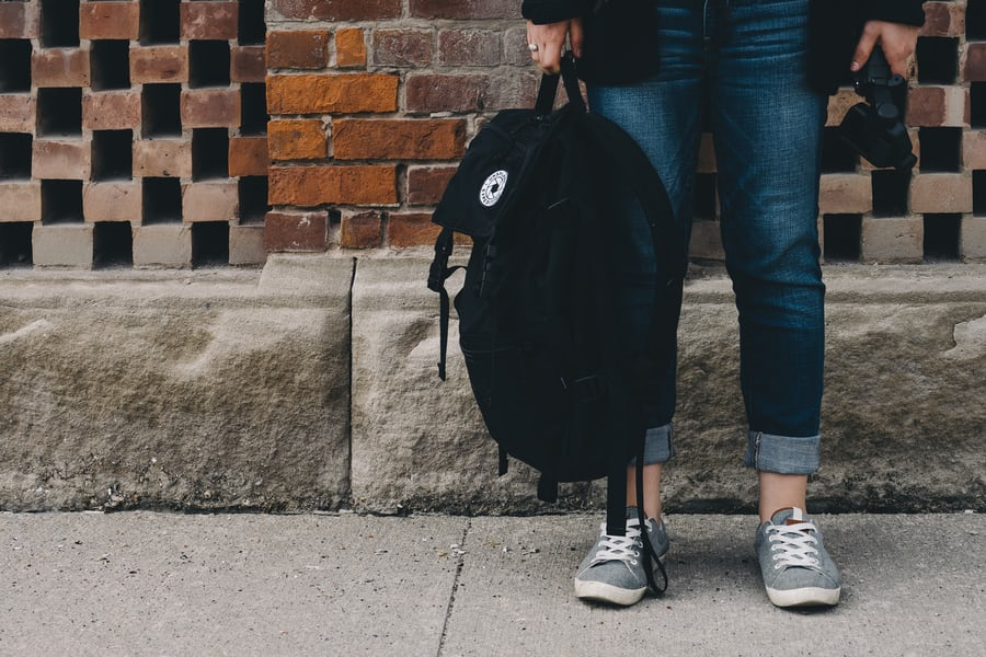 woman holding a backpack down by her legs