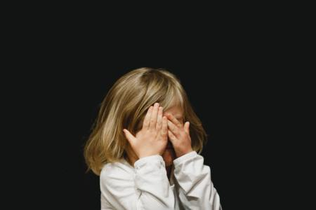 little girl covering face black background