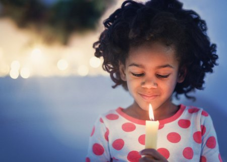 little girl holding candle looking down at it