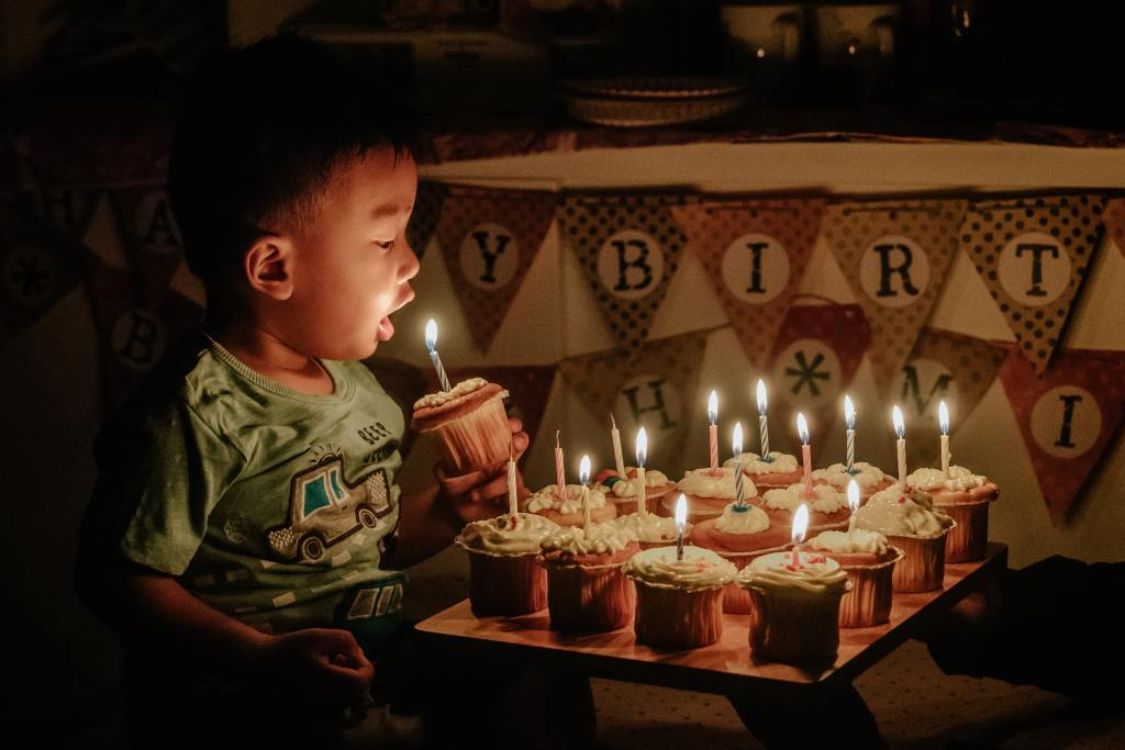 little boy blowing out candles on cupcakes