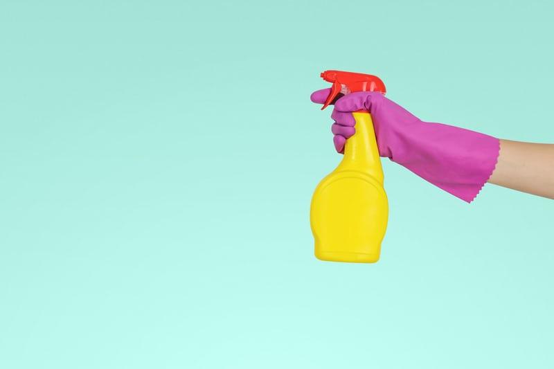 hand in purple glove holding spray bottle
