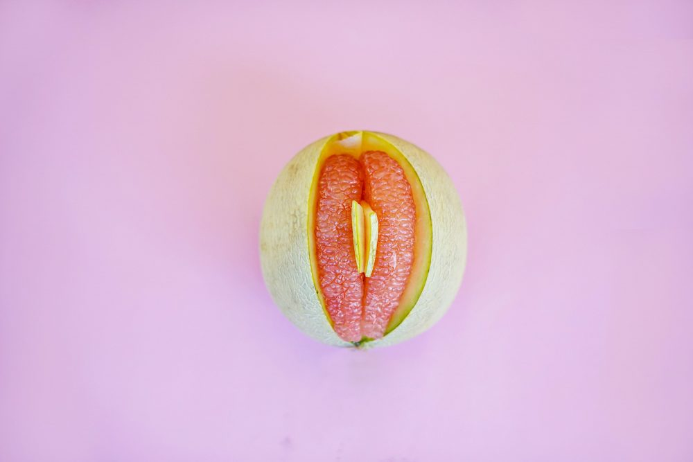 pomelo fruit on pink background that looks like a vagina