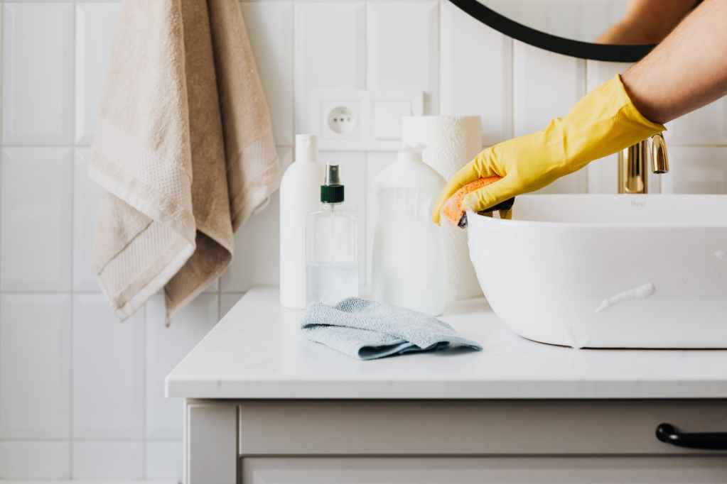 person in glove wiping surface of sink in modern bathroom