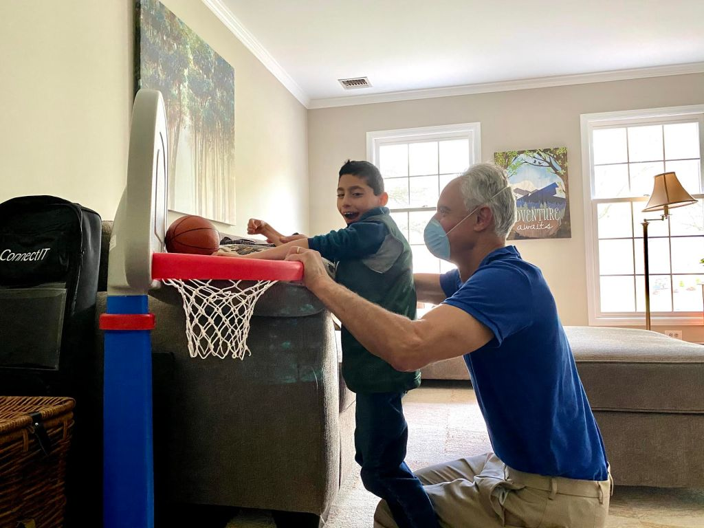 Eight-year-old with his physical therapist playing with an indoor plastic basketball hoop