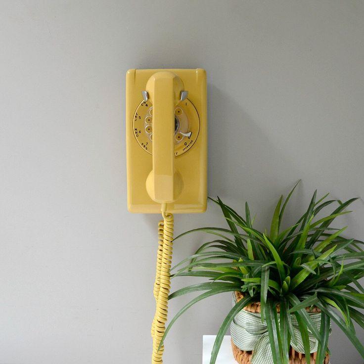 yellow wall mounted rotary phone