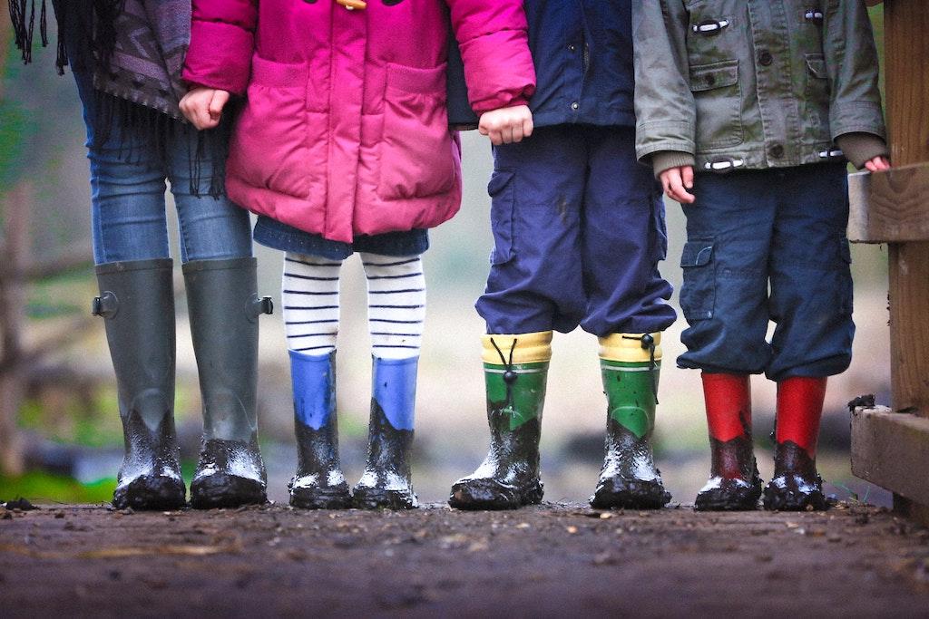 four children outside holding hands