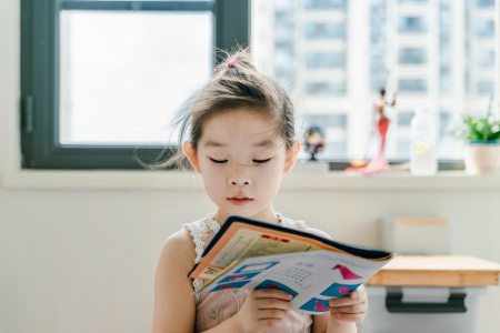 little girl reading book in front of window