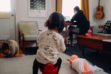 woman working from home, child in foreground