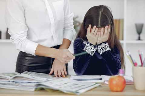 upset little girl sitting near crop woman in classroom
