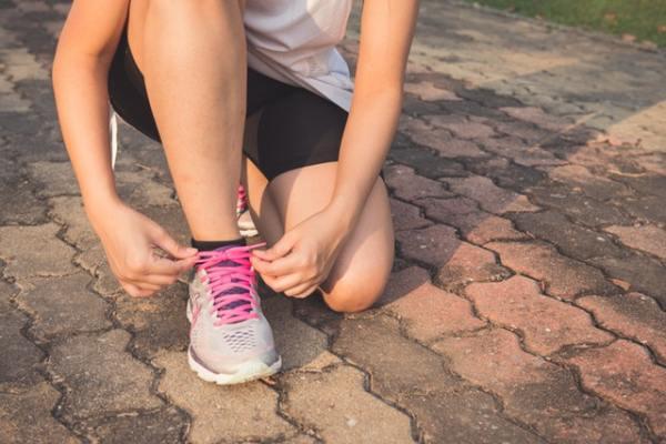 Früh aufstehen - Eine Frau in Sportsachen schnürt ihre Turnschuhe