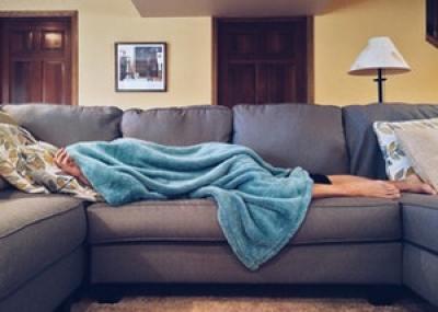 Motivation zum Sport Frau liegt auf der Couch mit Decke über dem Kopf