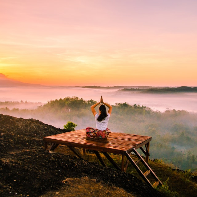 Entscheidungen treffen - Eine Frau die im Sonnenaufgang meditiert