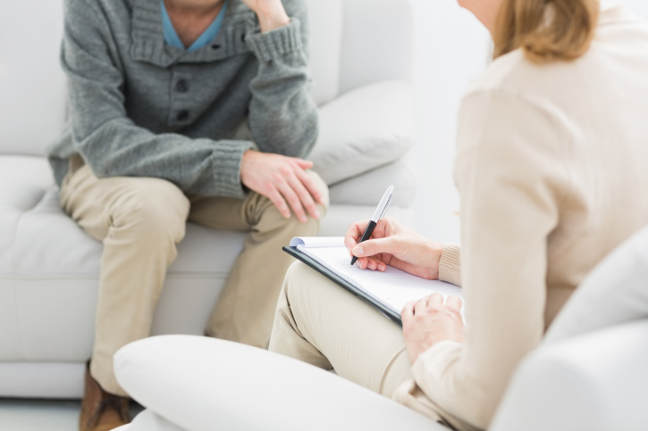 Man discussing anxiety symptoms with therapist
