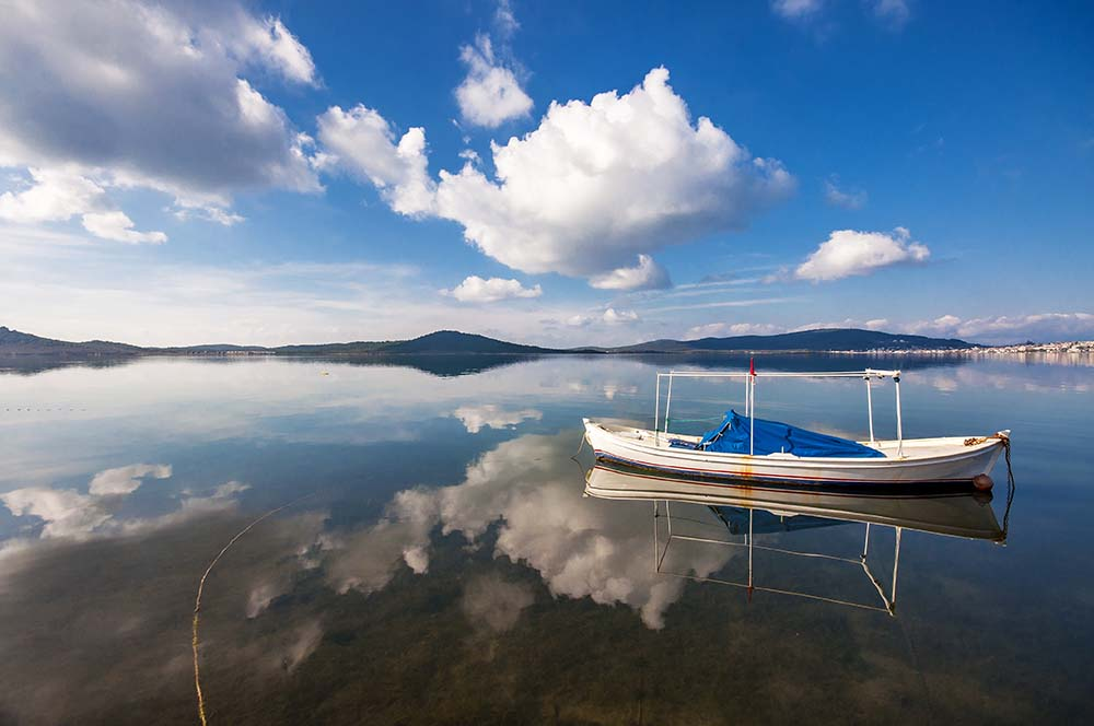 Fishing boat and clouds reflections at calm day in Ayvalik