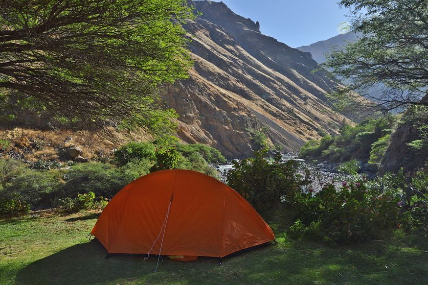 Оранжевая палатка в горах у реки