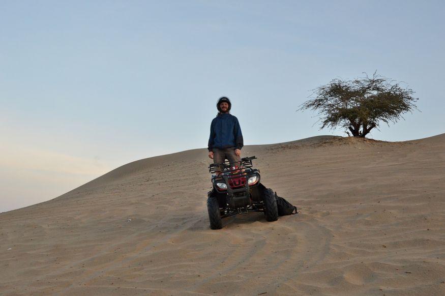 Парень на квадроцикле в пустыне