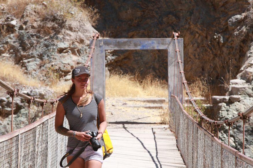 Девушка на подвесном мосту с фотоаппаратом в солнечный день