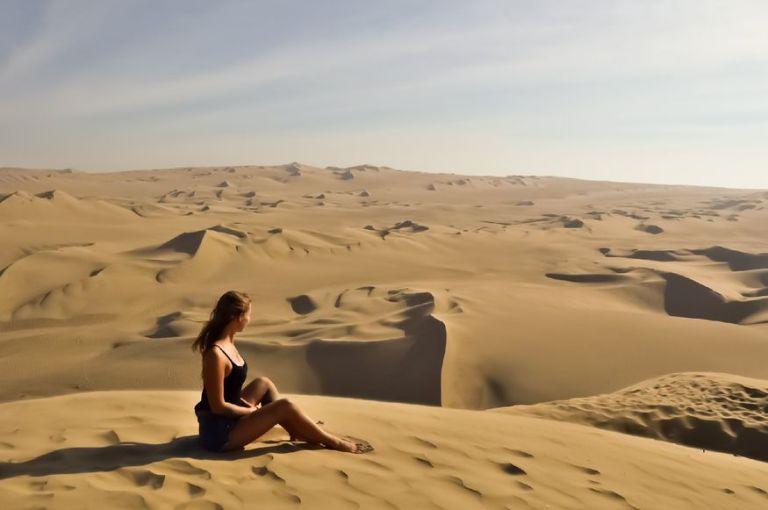 Девушка смотрит на желтую пустыню с высокой дюны