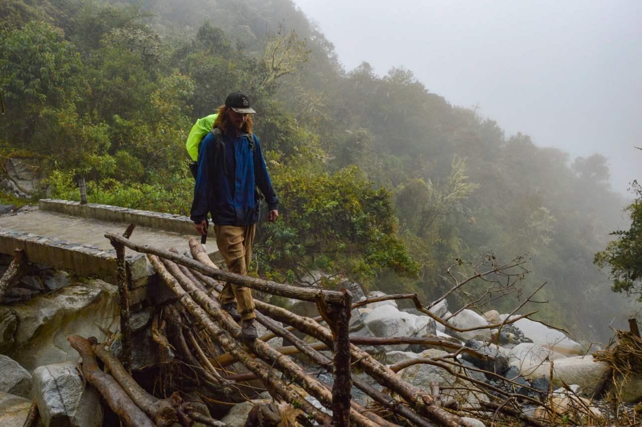 Мужчина переходит деревянный мост через реку