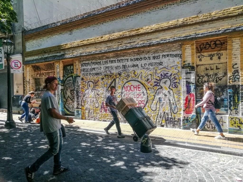 Парень толкает тележку с коробками на фоне стены с граффити
