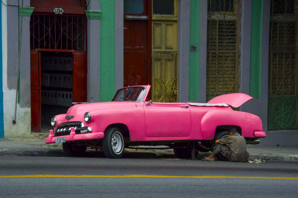 Кубинец ремонтирует колесо розового автомобиля